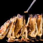 Berenjenas en tempura rellenas de marisco con salsa de moscatel y pasas