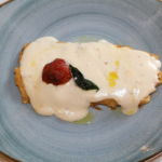Puerro relleno con jamón Ibérico, queso Raclette y baño de crema de oricios